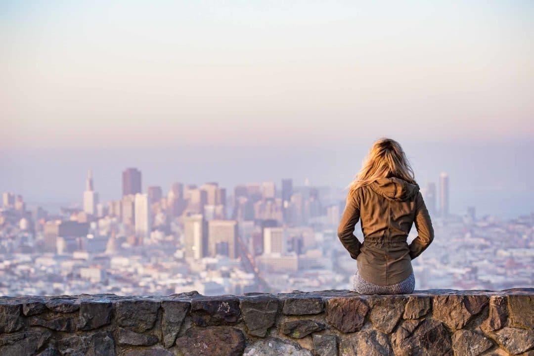 Mujer sentada contemplando la ciudad desde mirador